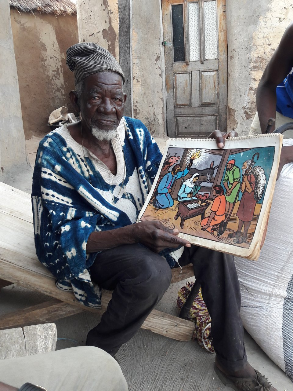 Koma chief holding illustration of the birth of Jesus