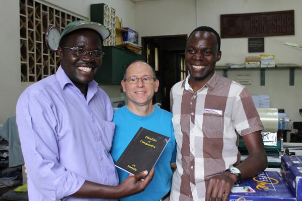 Image of men excited at receiving printed copies of Genesis and Exodus in Lunyole
